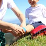 apteczka na wyjazd z dzieckiem uraz nogi małego dziecka na wakacjach zaopatrzony przez dorosłą osobę