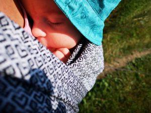 noworodek zawiązany w chustę do noszenia dzieci w upalny letni dzień z czapeczką na głowie